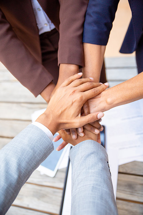 Successful business team expressing unity and putting their hands together. Closeup of people stacking hands. Team success or support concept